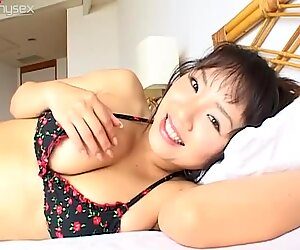 Giggling busty bitch Harumi Nemoto lies on the bed and waits for a cock