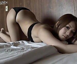 Accattivante seduttrice asiatica sdraiata sul letto in bikini